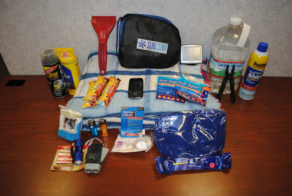things to carry in your car boot in winter: Winter survival kit for car boot includes a fully-charged prepaid mobile phone, a multi-tool, blanket, snacks, water, deicer, ice scraper